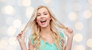Mujer joven sonriente que sostiene su filamento del pelo Fotografía de archivo libre de regalías