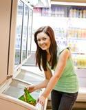 Mujer joven sonriente que sostiene un producto congelado Imágenes de archivo libres de regalías