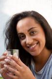 Mujer joven sonriente que sostiene un vidrio de agua Foto de archivo