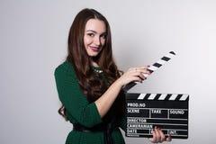Mujer joven sonriente que sostiene una chapaleta de la película Fotografía de archivo libre de regalías