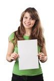 Mujer joven sonriente que sostiene una tarjeta en blanco blanca. Imagen de archivo