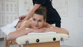 Mujer joven sonriente que tiene masaje de relajación en la parte posterior en salón del balneario metrajes