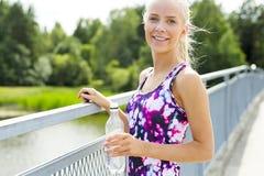 Mujer joven sonriente que tiene su rotura después de correr Foto de archivo libre de regalías