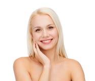 Mujer joven sonriente que toca su piel de la cara Imágenes de archivo libres de regalías