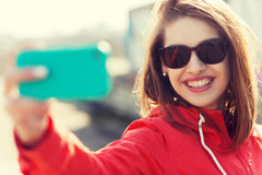 Mujer joven sonriente que toma el selfie con smartphone Imagenes de archivo