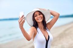 Mujer joven sonriente que toma el selfie con smartphone Foto de archivo