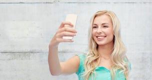 Mujer joven sonriente que toma el selfie con smartphone Fotografía de archivo libre de regalías