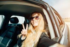 Mujer joven sonriente que toma la imagen del selfie con la cámara elegante del teléfono al aire libre en coche Imagenes de archivo