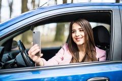Mujer joven sonriente que toma la imagen del selfie con la cámara elegante del teléfono al aire libre en coche Foto de archivo