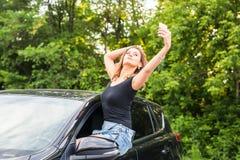 Mujer joven sonriente que toma la imagen del selfie con la cámara elegante del teléfono al aire libre en coche Fotos de archivo