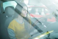 Mujer joven sonriente que toma la imagen del selfie con la cámara elegante del teléfono en coche Imágenes de archivo libres de regalías