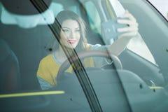 Mujer joven sonriente que toma la imagen del selfie con la cámara elegante del teléfono en coche Imagen de archivo