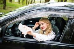 Mujer joven sonriente que toma la imagen del selfie con la cámara elegante del teléfono en coche Imagenes de archivo