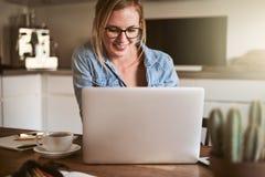 Mujer joven sonriente que trabaja en su negocio en casa imagen de archivo libre de regalías