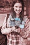Mujer joven sonriente que trabaja en su smartphone futurista Imágenes de archivo libres de regalías
