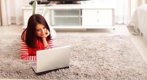 Mujer joven sonriente que usa el ordenador portátil Fotografía de archivo libre de regalías