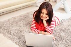 Mujer joven sonriente que usa el ordenador portátil Foto de archivo libre de regalías