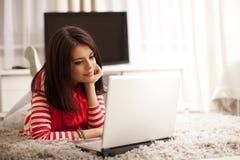 mujer joven sonriente que usa el ordenador portátil Fotos de archivo libres de regalías