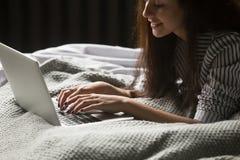 Mujer joven sonriente que usa el ordenador portátil que miente en la cama, cierre para arriba Imagenes de archivo