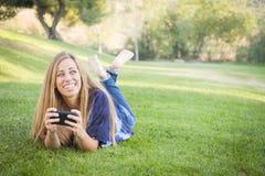 Mujer joven sonriente que usa el teléfono celular al aire libre Imagenes de archivo