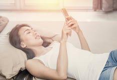 Mujer joven sonriente que usa el teléfono celular en cama Fotografía de archivo libre de regalías