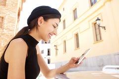 Mujer joven sonriente que usa el teléfono móvil Fotografía de archivo libre de regalías