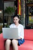 Mujer joven sonriente que usa la computadora portátil Foto de archivo libre de regalías