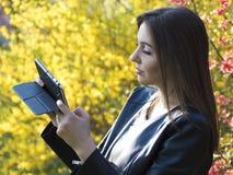 Mujer joven sonriente que usa la tableta en parque Foto de archivo