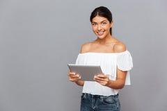 Mujer joven sonriente que usa la tableta y la mirada de la cámara Fotos de archivo libres de regalías