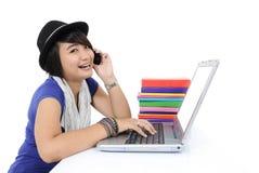 Mujer joven sonriente que usa un ordenador portátil Foto de archivo libre de regalías