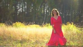 Mujer joven sonriente romántica de la belleza en el baile rojo largo del vestido en el bosque en puesta del sol Muchacha modelo f almacen de video