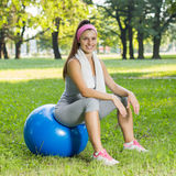 Mujer joven sonriente sana de la aptitud que descansa sobre la bola de Pilates Fotografía de archivo