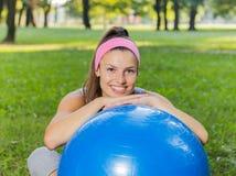 Mujer joven sonriente sana de la aptitud que descansa sobre la bola de Pilates Fotografía de archivo libre de regalías