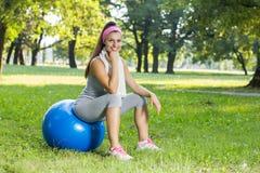 Mujer joven sonriente sana de la aptitud que descansa sobre la bola de Pilates Foto de archivo