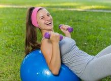 Mujer joven sonriente sana de la aptitud que descansa sobre la bola de Pilates Imagen de archivo