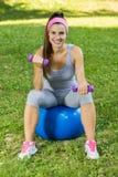 Mujer joven sonriente sana de la aptitud que descansa sobre la bola de Pilates Imagenes de archivo