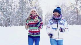 Mujer joven sonriente y hombre joven hermoso que activan junto en el bosque del invierno almacen de video