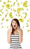 Mujer joven sorprendente que mira en caer abajo euros Fotos de archivo