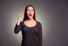 Mujer joven sorprendente que señala hacia arriba Imagen de archivo libre de regalías