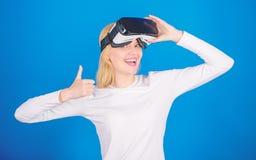 Mujer joven sorprendente que toca el aire durante la experiencia de VR Mujer que mira la visi?n de la realidad virtual Mujer jove imagen de archivo libre de regalías