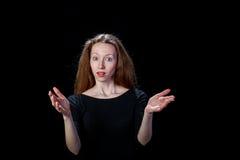 Mujer joven sorprendida con el pelo marrón en un fondo negro Fotografía de archivo libre de regalías