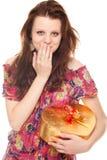 Mujer joven sorprendida con el rectángulo del oro del regalo como corazón Fotografía de archivo libre de regalías