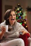 Mujer joven sorprendida con la taza de chocolate caliente que ve la TV Imágenes de archivo libres de regalías