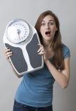 Mujer joven sorprendida con las escalas en manos Imágenes de archivo libres de regalías
