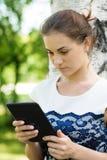 Mujer joven sorprendida con una tableta Fotos de archivo libres de regalías