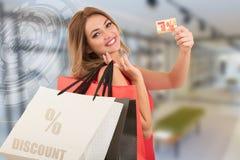 Mujer joven sorprendida emocionada alegre con la tarjeta de crédito con el ejemplo de la venta Imagenes de archivo