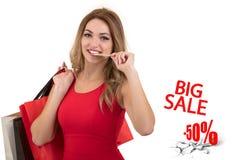 Mujer joven sorprendida emocionada alegre con la tarjeta de crédito con el ejemplo de la venta Fotos de archivo