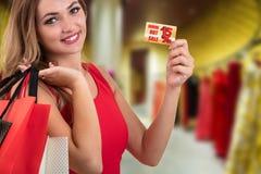 Mujer joven sorprendida emocionada alegre con la tarjeta de crédito en la alameda de compras Imagen de archivo libre de regalías