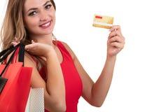 Mujer joven sorprendida emocionada alegre con la tarjeta de crédito sobre el fondo blanco Foto de archivo