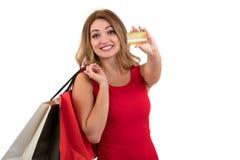 Mujer joven sorprendida emocionada alegre con la tarjeta de crédito sobre el fondo blanco Imágenes de archivo libres de regalías